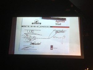 De handtekening van minister Kamp op het scherm in de zaal.