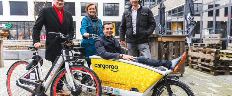 Groepsportret van vier mensen van projectontwikkelaar AM in Delft die poseren met een eletrische fiets en een bakfiets voor vrachtvervoer, waar één van de vier geportretteerden is gaan zitten