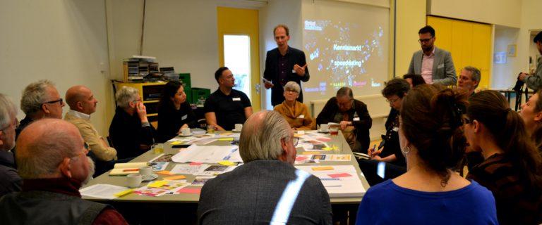 Bewoners en professionals in gesprek aan een grote tafel vol met post-it briefjes tijdens de kennismarkt van het stadslab Vergrijzing op 7 februari