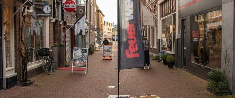 Een bankje dat bestaat uit twee zitdelen die haaks op elkaar geplaatst zijn, voorzien van een vlag met de tekst 'Feuerwehr', midden op de Oosterstraat in Leeuwarden
