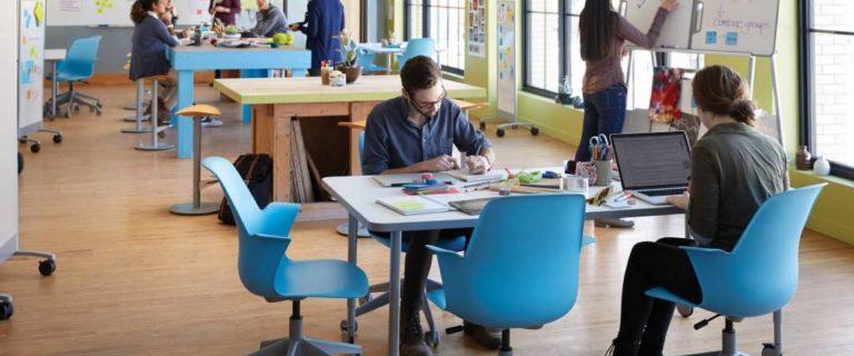 Studenten aan het werk aan tafels in een creatieve werkruimte