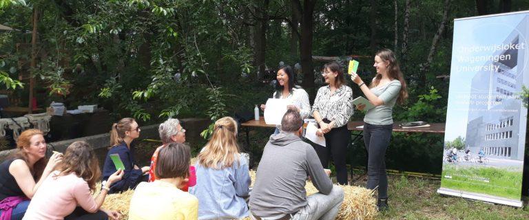 In een groene tuin zien we publiek zitten op hooibalen terwijl drie dames van Wageningen University stellingen voorlezen waar het publiek op reageert door gekleurde kaarten omhoog te houden