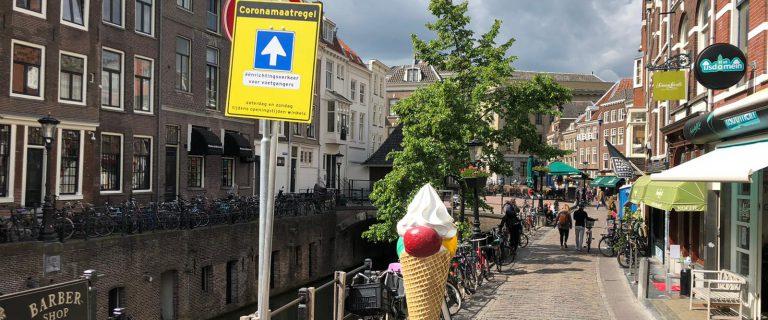 Foto toont een Utrechtse gracht met een verkeersbord dat het icoon voor een eenrichtingsverkeersweg toont en de tekst 'Coronamaatregel'.