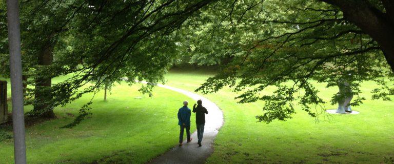 We zien twee mensen wandelend en pratend op een voetpad door een bos. Het beeld is ingekaderd door een grote boom die over het pad en de wandelaars buigt