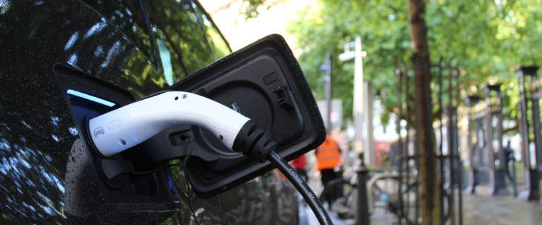 Een detail van een elektrische auto in de oplader.